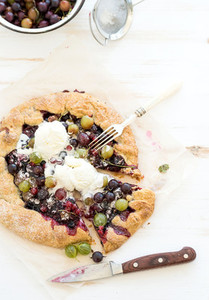Summer crostata or galette pie with fresh garden berries and vanilla ice cream over white wooden background top view