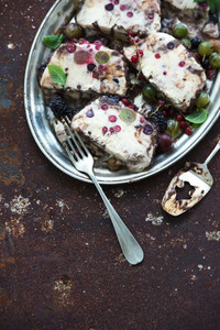 Semifreddo or italian cheese ice cream dessert with garden berries and mint on vintage silver tray over metal rusty grunge background  top view