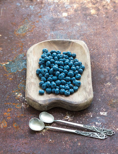 Blueberries in a rustic wooden serving dish over grunge metal rusty background  top view