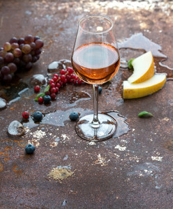 Glass of rose wine with berries  melon  grapes and ice on grunge rusty metal background