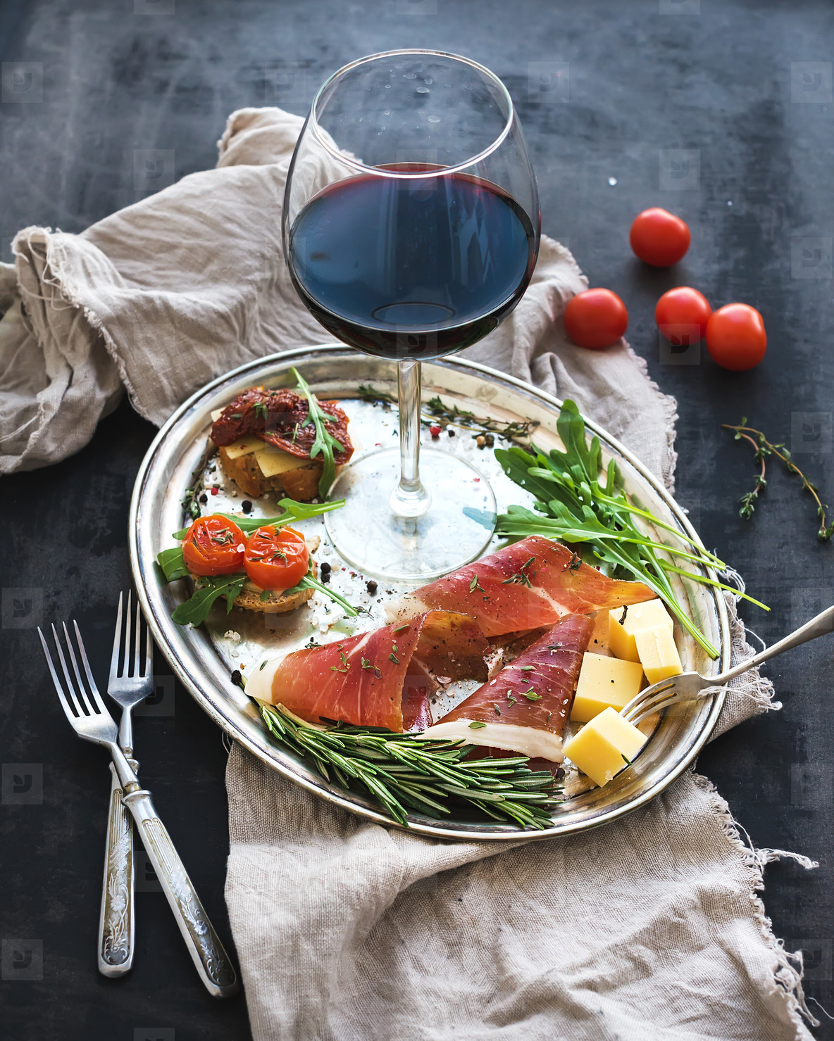 Wine appetizer set  Glass of red wine  vintage dinnerware  brushetta with cherry  dried tomatoes  arugula  parmesan  smoked meat on silver tray over rustic grunge surface