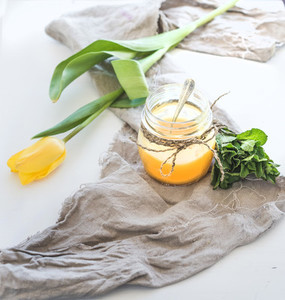 Lemon curd in a jar  bunch of fresh mint and tulip over rustic dark backdrop