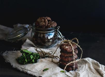 Dark chocolate chip cookies with fresh mint on dark backdrop