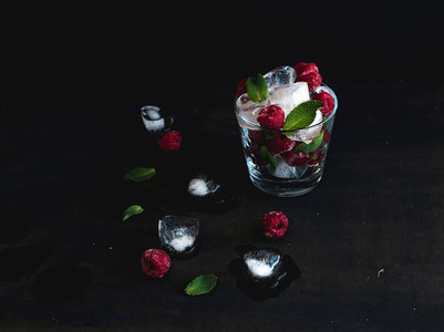 Ice cubes with mint leaves and frozen raspberry in glass on grunge dark background