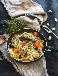 Pasta spaghetti with pesto sauce  basil  cherry tomatoes  garlic and thyme in a cooking pan on old grunge dark table