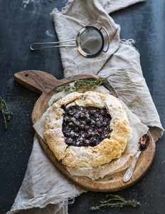 Homemade crusty pie or galette with blueberries  thyme and ice cream on rustic wooden board over dark backdrop