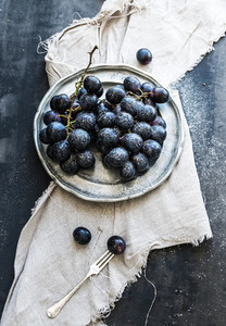 Bunch of fresh grapes in rustic vetal plate on dark grunge background