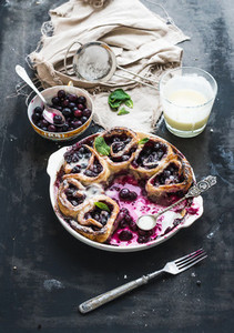 Blueberry buns with fresh mint and creamy sauce on dark backdrop