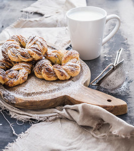 Cinnamon buns with sugar powder on rustic wooden board  mug of milk   dark grunge surface
