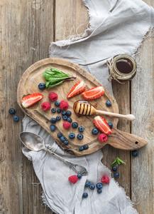 Blueberries  raspberries  strawberries  honey and fresh mint onver  rustic chopping board over wood backdrop