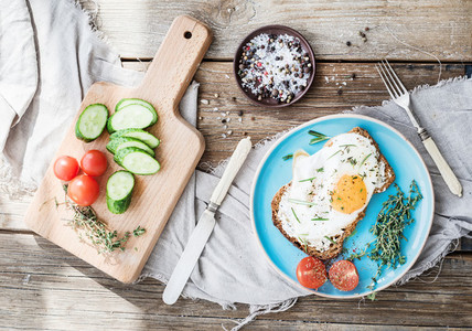 Breakfast set  Whole grain sandwich with fried egg  vegetables and herbs