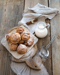 Cinnamon buns with sugar powder on rustic wooden board jug of milk  dark grunge surface