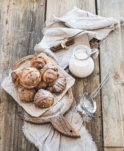 Cinnamon buns with sugar powder on rustic wooden board  jug of milk   dark grunge surface