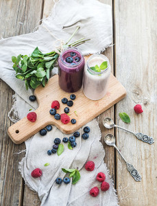 Fresh healthy smoothie with blueberries  raspberries in glass jars and mint