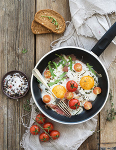 Pan of fried eggs  bacon and cherry tomatoes with bread on rustic wood table surface