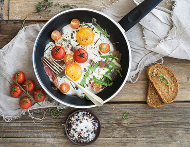 Pan of fried eggs  bacon and cherry tomatoes with bread