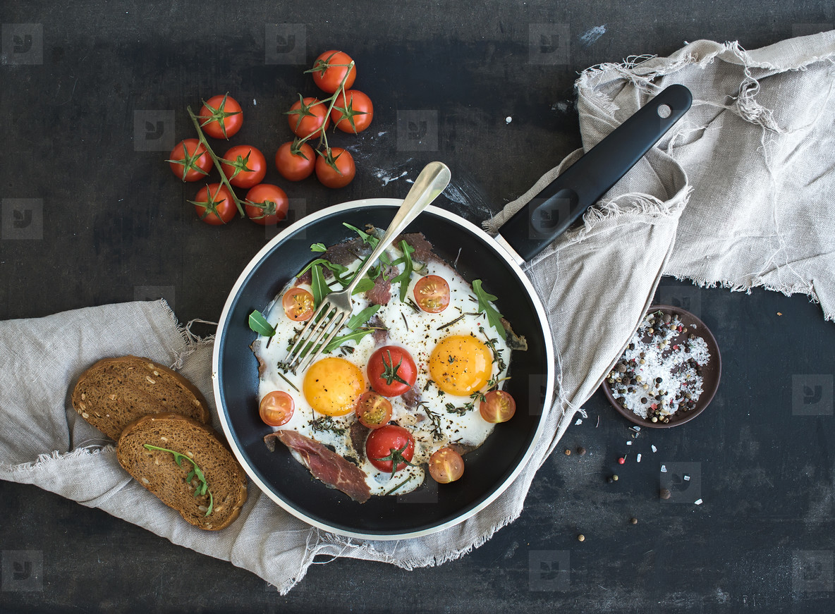 Pan of fried eggs  bacon and cherry tomatoes with bread on dark table surface