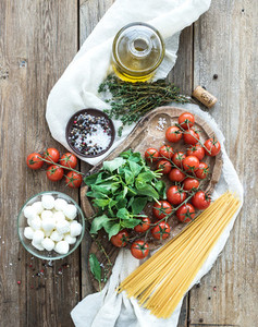 Ingredients for cooking pasta  Spaghetti  basil  cherry tomatoes  mozarella  olive oil  thyme  salt  spices on rustic chopping board over old wood background