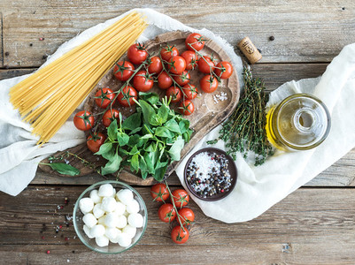 Ingredients for cooking pasta  Spaghetti  basil  cherry tomatoes  mozarella  olive oil