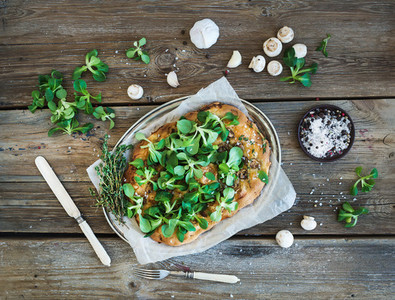 Rustic homemade pizza with fresh lamb s lettuce  mushrooms and garlic over rough wooden background