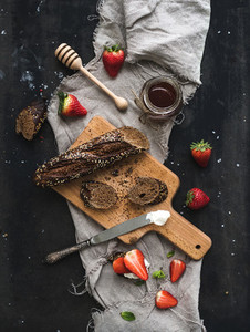 Breakfast set Black baguette toasts with fresh strawberries honey and mascarpone cheese on dark grunge table surface