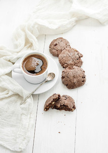 Chocolate cookies with almond and cranberries  cup of coffee  white wooden backdrop