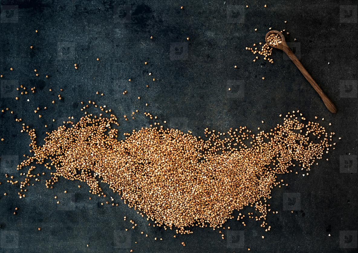Brown buckwheat groats on dark grunge background