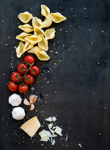 Food frame Pasta ingredients Cherry tomatoes pasta garlic basil parmesan and spices on dark grunge backdrop copy space