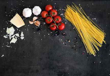Food frame  Pasta ingredients  Cherry tomatoes  spaghetti pasta  garlic  basil  parmesan and spices on dark grunge backdrop  copy space  horizontal oriented