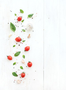Cherry tomatoes  fresh basil leaves  garlic cloves and spices on rustic white wooden backdrop  top view