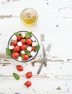 Caprese salad cherry tomatoes and mozzarella in metal bowl with olive oil on rustic white wooden backdrop  top view