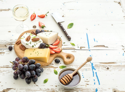 Cheese appetizer selection or wine snack set  Variety of cheese  grapes  pecan nuts  strawberry and honey on round wooden board over rustic white backdrop  top view
