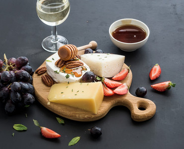 Cheese appetizer selection or whine snack set  Variety of cheese  grapes  pecan nuts  strawberry and honey on round wooden board over black backdrop
