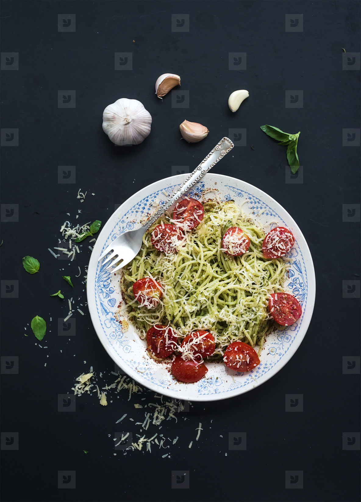 Pasta spaghetti with pesto sauce  basil  garlic  baked cherry tomatoes on rustic dark table  top view