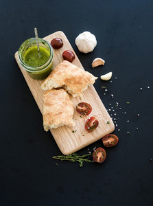 Pesto sauce in jar ciabatta bread cherry tometoes thyme and garlic on rustic wooden board over black grunge backdrop