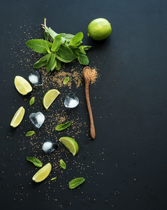 Ingredients for mojito  Fresh mint  limes  ice  sugar over black backdrop  Top view