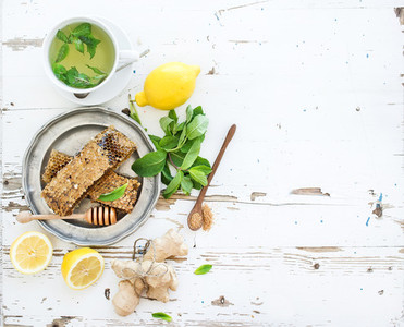 Cup of herbal tea with fresh mint  honey  lemon  ginger on rustic white wooden background  Top view