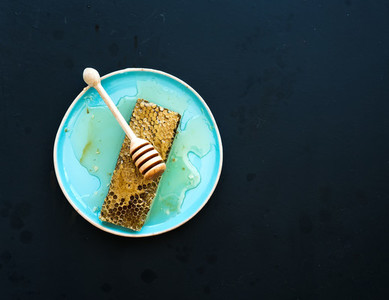 Honeycomb with honey dipper on blue ceramic plate over black background  top view