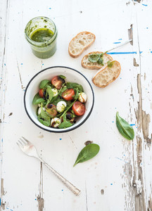 Caprese salad  chiabatta slices  Cherry tomatoes  baby spinach and mozzarella in metal bowl with pesto dressing on rustic white wooden backdrop