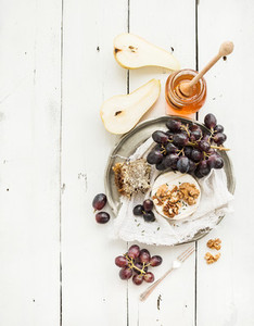 Camembert cheese with grape  walnuts  pear and honey on vintage metal plate over white rustic wood backdrop  top view