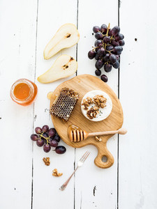 Camembert cheese with grape  walnuts  pear and honey on oak serving board over white rustic wood backdrop  top view