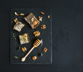 Honeycomb  walnuts and honey dipper on black slate tray over grunge dark backdrop  top view