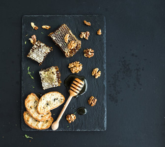 Honeycomb  walnuts  bread slices and honey dipper on black slate tray over grunge dark backdrop  top view