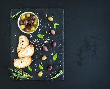 Mediterranean olives with herbs and ciabatta slices on black slate tray over dark grunge background  top view