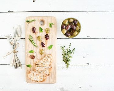 Mediterranean olives with herbs and ciabatta slices on rustic wooden board  over white background  top view