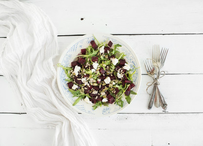 Beetroot salad with arugula  feta cheese  red salt and pumpkin seeds in vintage plate over white rustic wooden background  top view