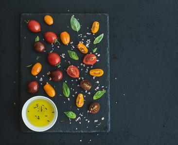 Cherry tomatoes of various color  basil leaves  spices and olive oil on black slate tray over dark grunge background  Top view
