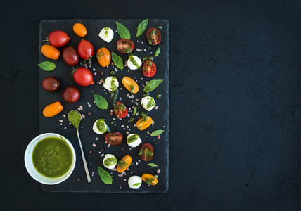 Caprese set  Cherry tomatoes of various color  mozarella  basil leaves  spices and pesto sauce on black slate tray over dark grunge background  Top view