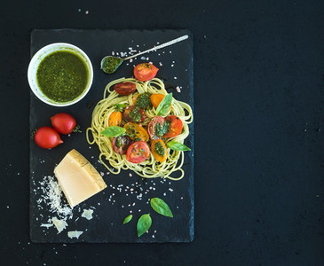 Spaghetti with pesto sauce roasted cherry tomatoes fresh basil and parmesan cheese on black stone serving board over dark grunge backdrop Top view