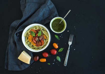 Pasta spaghetti with pesto sauce  basil  slow roasted cherry tomatoes in rustic metal bowl on dark grunge backdrop  top view